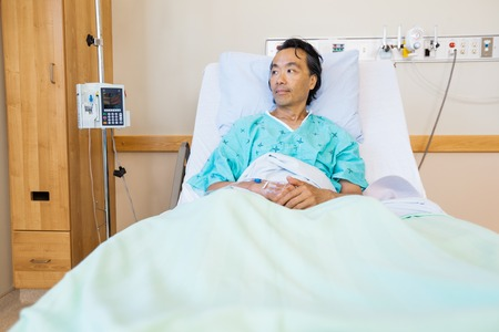 asia people: Thoughtful mature male patient reclining on bed while looking away in hospital Stock Photo