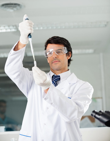 researcher: Confident male scientist filling solution into test tube in medical lab