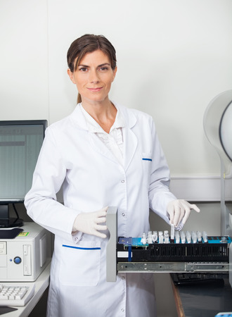 coagulation: Portrait of female researcher with samples for coagulation analysis in lab