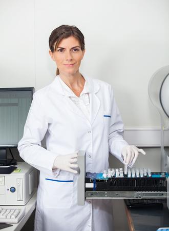 Ritratto di ricercatore femminile con campioni per analisi della coagulazione in laboratorio photo