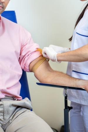 Sezione centrale di infermiere preparazione del paziente per il test del sangue in laboratorio photo