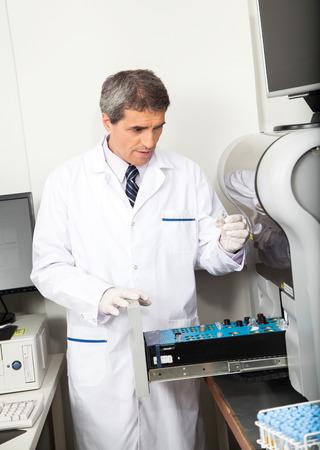 Analizzatore maschio maturo scienziato di carico con i campioni in laboratorio photo