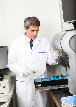 analyzer: Mature male scientist loading analyzer with samples in laboratory Stock Photo