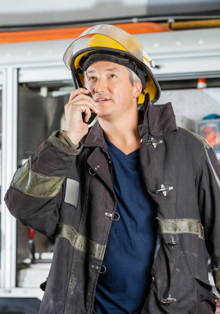 walkie: Mature fireman looking away while using walkie talkie at fire station Stock Photo