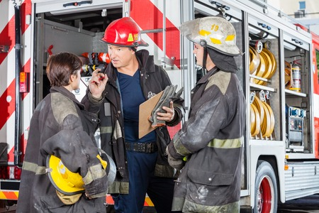 firefighter: Male firefighter discussing with colleagues while holding clipboard against truck at fire station
