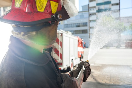 firefighter: Side view of male firefighter spraying water while practicing at fire station