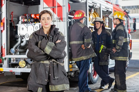 female clothing: Portrait of confident firewoman with male colleagues discussing by truck in background at fire station