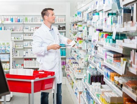Metà adulto maschio farmacista contando stock, mentre tiene tablet computer in farmacia
