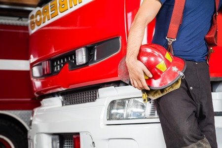 leaning on the truck: Midsection of young fireman holding red helmet while leaning on firetruck at station