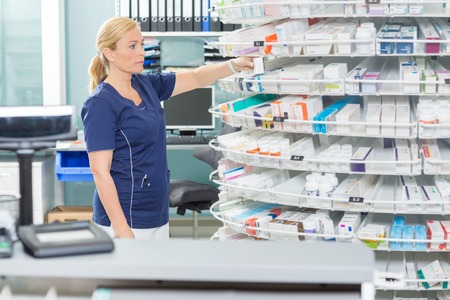 arranging: Female chemist arranging products in shelves at pharmacy