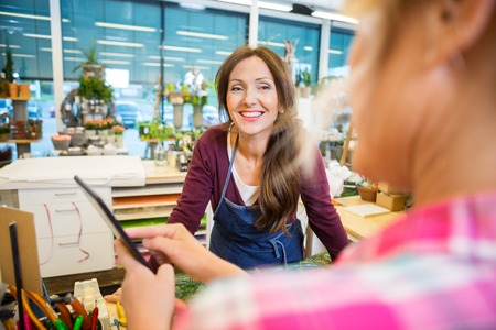 selling service smile: Happy florist looking at female customer using digital tablet in flower shop Stock Photo