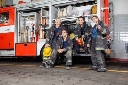 Quipe de pompiers réfléchie regardant ailleurs par camion de pompier à la station Banque d'images - 43648466