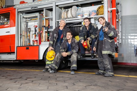 firetruck: Team of thoughtful firefighters looking away by firetruck at station Stock Photo