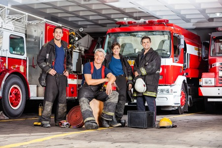engine fire: Portrait of happy firefighters team with equipment against trucks at fire station