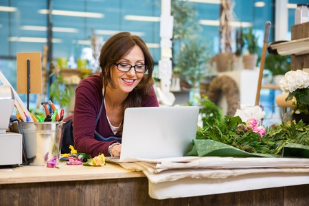 vendedor: Floristería mujer feliz mediados de adultos usando la computadora portátil en el contador en la tienda de flores