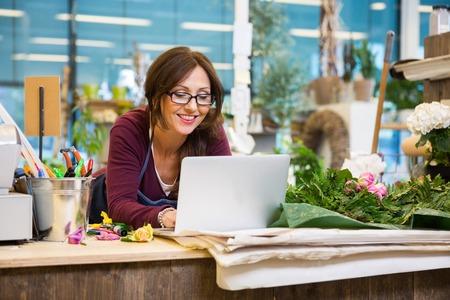 Glücklich Mitte der erwachsenen weiblichen Floristen mit Laptop zu Zähler in Blumenladen