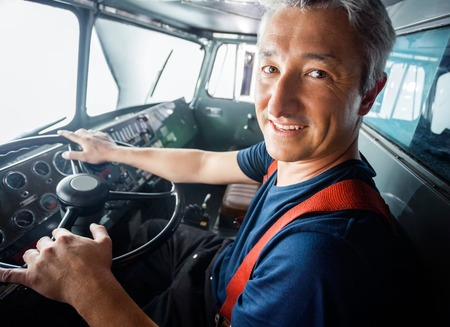 engine fire: Portrait of happy mature firefighter driving firetruck