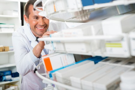 pharmacy: Mid adult male chemist counting stock in pharmacy Stock Photo