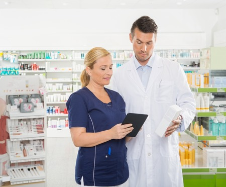 work together: Female assistant using digital tablet while male pharmacist holding product in pharmacy Stock Photo