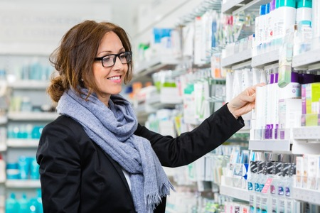 Smiling female consumer choosing product in pharmacy Stock Photo