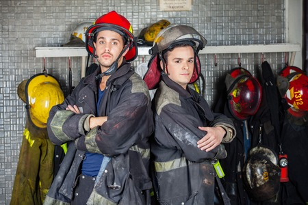 protective suit: Portrait of confident firefighters standing arms crossed at fire station