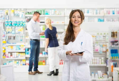 retail occupation: Portrait of smiling female chemist holding digital tablet while assistant and customer standing in background at pharmacy