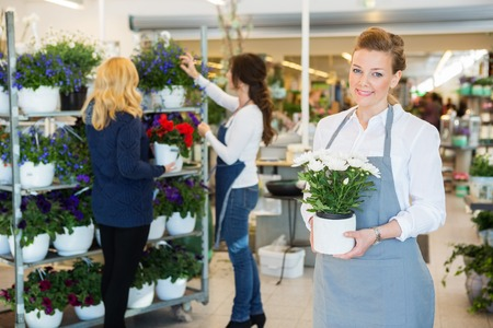 girl holding flower: Portrait of happy florist holding flower pot with colleague assisting customer in background at shop