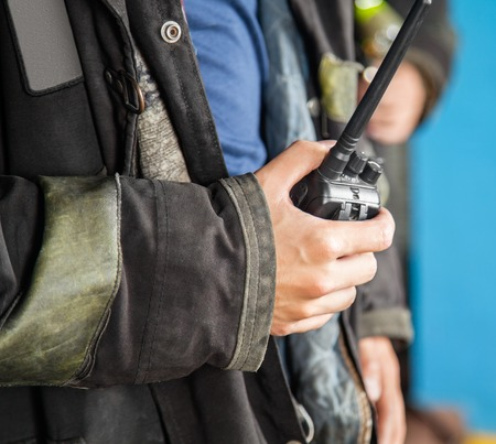 talkie: Midsection of firefighter holding walkie talkie at fire station Stock Photo