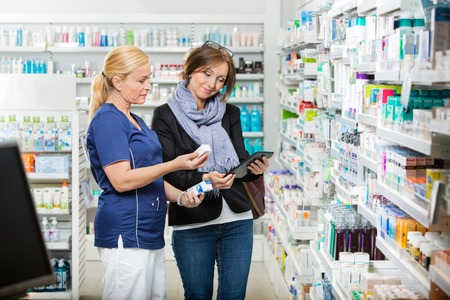 assistants: Smiling female chemist holding eye drops while customer using digital tablet in pharmacy