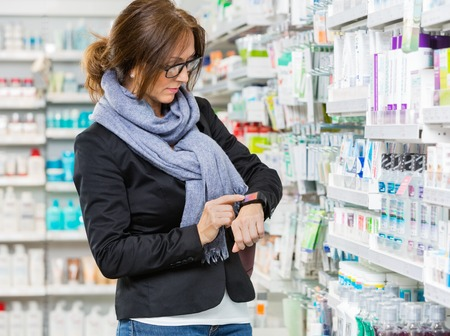 healthcare: Mid adult female consumer in casuals using smartwatch in pharmacy Stock Photo
