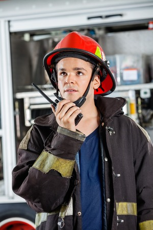 talkie: Confident young firefighter looking away while using walkie talkie at fire station