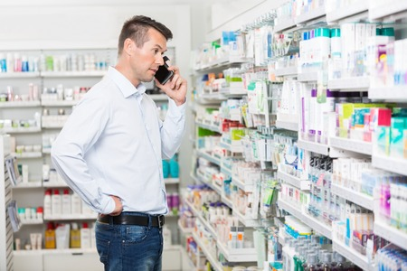 pharmaceutic: Confused mid adult man using mobile phone while looking at products in pharmacy