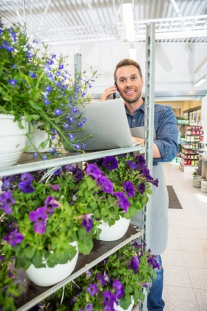 mobile business: Portrait of male florist using mobile phone and laptop in flower shop