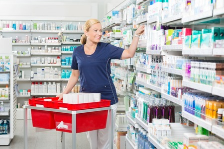 arranging: Smiling mature female chemist arranging products in pharmacy