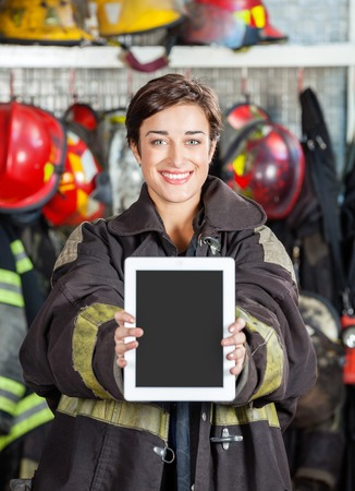 firefighter: Portrait of happy firewoman showing digital tablet at fire station