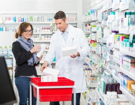 medicina: Sonreír farmacias mostrando medicamentos masculinos para el cliente femenino en la farmacia
