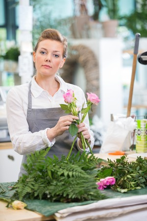 floral arrangements: Portrait of florist making rose bouquet at counter in flower shop