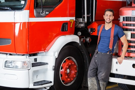 leaning on the truck: Portrait of confident firefighter leaning on truck at fire station Stock Photo