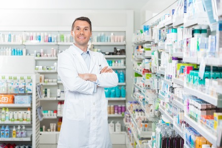 pharmacy store: Portrait of smiling mid adult male pharmacist standing arms crossed in pharmacy Stock Photo