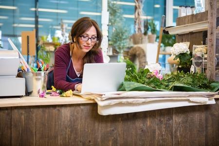 sexo femenino: Florister�a mujer adulta mediados usando la computadora port�til en el contador en la tienda de flores