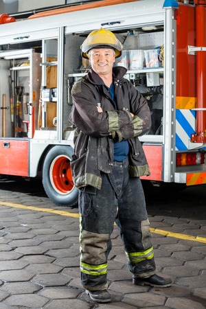 arms crossed: Portrait of happy fireman standing arms crossed against truck at fire station Stock Photo
