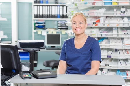 Portrait of confident assistant sitting at cash counter in pharmacy Banco de Imagens