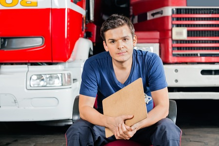 firefighter: Portrait of confident male firefighter holding clipboard while sitting against firetrucks at station Stock Photo