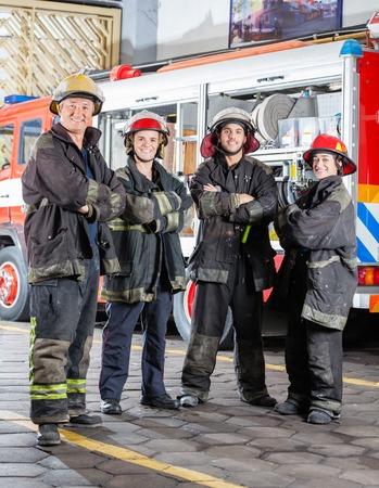 bombero: Retrato de cuerpo entero de los bomberos seguros de pie brazos cruzados en la estaci�n de bomberos