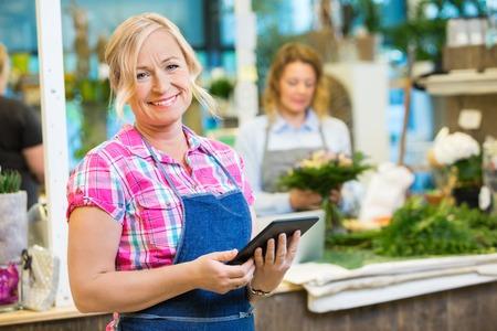 Ritratto di sorridere maturo fiorista femminile in possesso di tavoletta digitale con il collega che lavora in background presso il negozio