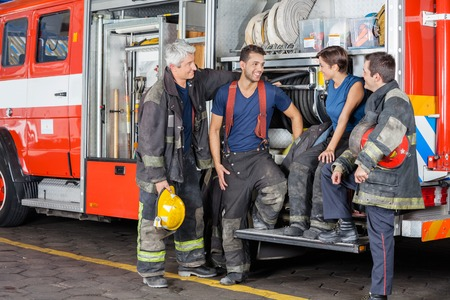 leaning on the truck: Team of smiling firefighters conversing by firetruck at station