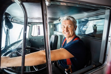 truck driver: Portrait of happy mature fireman driving firetruck at station Stock Photo