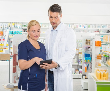 work together: Female assistant using tablet computer with male pharmacist while standing in pharmacy