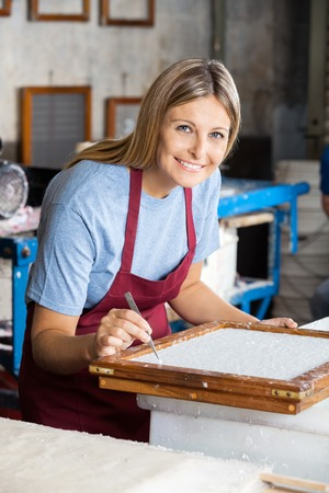 mid adult female: Portrait of mid adult female worker cleaning paper with tweezers in factory Stock Photo