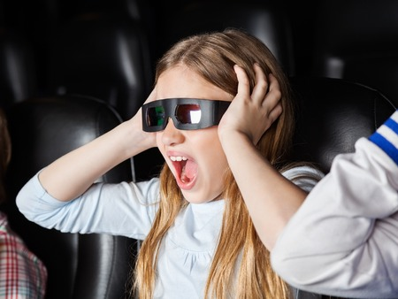 screaming: Scared girl screaming while watching 3D movie in cinema theater Stock Photo